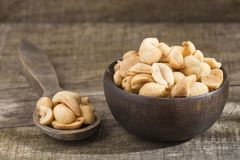 Toasted peanuts on wooden background - Arachis hypogaea stock images