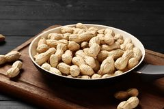 Peanuts in a frying pan on the kitchen board royalty free stock photo