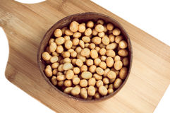 Peanuts in glaze shell in a round plate on a cutting board isola Royalty Free Stock Image