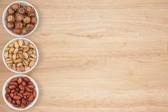 Peanuts, hazelnuts, pistachios in a cyan bowl Stock Image