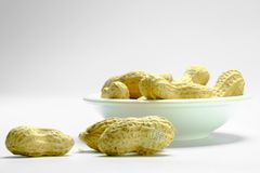 Peanuts isolated on the white background. Close up in blow. royalty free stock image