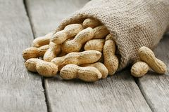 Peanuts in a miniature burlap bag on old, gray wooden surface royalty free stock photography