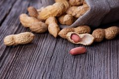 Peanuts in a miniature burlap bag on wooden Royalty Free Stock Image
