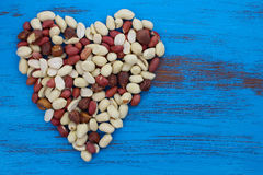 Peanuts nuts in heart shape on blue rustic wood background. Royalty Free Stock Photo
