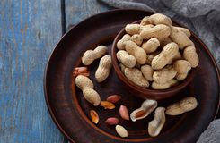 Peanuts in nutshell and peeled peanut on wooden background. Healthy and dietary nutrition. Raw food.  stock image