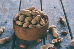 Peanuts in nutshell and peeled peanut on wooden background. Healthy and dietary nutrition. Raw food.  stock photography