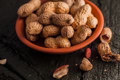 Peanuts in nutshell on a piece of wood. Many roasted peanuts on the wooden texture Royalty Free Stock Image