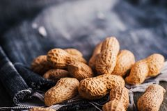 Peanuts in nutshell on a piece of wood. Many roasted peanuts on the wooden texture Stock Image