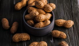 Peanuts in nutshell on a piece of wood. Many roasted peanuts on the wooden texture Stock Photo