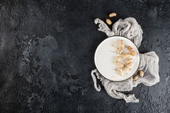 Peanuts in shell. Peanuts in nutshell on a white plate with napkin on black background. Top view with plase for text Royalty Free Stock Images
