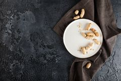 Peanuts in shell. Peanuts in nutshell on a white plate with napkin on black background. Top view with plase for text Royalty Free Stock Image