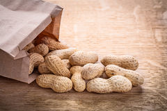 Peanuts paper bag on wooden board food and drink royalty free stock images