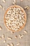 Peanuts in the peel on a light burlap. stock photos