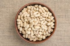Peanuts in the peel on a light burlap. royalty free stock photography