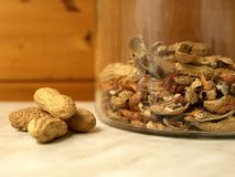 Peanuts and peels. In a glass. Close-up Stock Images
