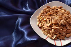 Peanuts in a plate on silk bakground Stock Images