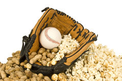 Peanuts, Popcorn, and Baseball. A baseball glove holds a hardball, peanuts, and popcorn.  It sits on a bed of nuts and popcorn Stock Image