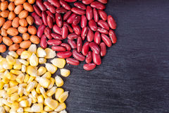 Peanuts and red beans and corn on black wooden board. Stock Photo