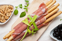 Grissini. Bread sticks with ham, olives fresh oregano herbs and peanuts royalty free stock images