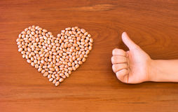 Peanuts shaped into a heart next to a thumbs up on a wooden surface. Heart health theme for better eating. Peanuts Royalty Free Stock Image