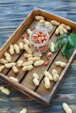 Glass jar with peeled peanuts. Stock Image