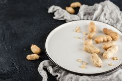 Peanuts in shell. Peanuts in nutshell on a white plate with napkin on black background Stock Photos
