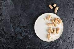Peanuts in shell. Peanuts in nutshell on a white plate with napkin on black background. Top view with plase for text Stock Images
