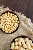 Peanuts in the shell and peeled closeup in a cup royalty free stock photos