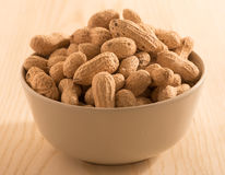 Peanuts with shell  in a white bowl on wooden background. Stock Photo