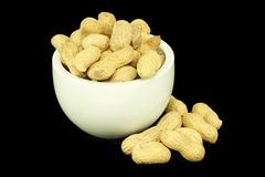 Peanuts with shells in a bowl. Black background Royalty Free Stock Photos