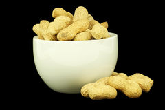 Peanuts with shells in a bowl. Black background Stock Photography