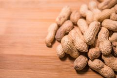 Peanuts in shells on a natural wooden surface royalty free stock photo