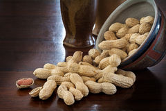 Peanuts in shells and rustic ceramic tableware on a dark table Stock Photo