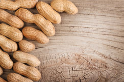 Peanuts in shells on wood background Stock Photos