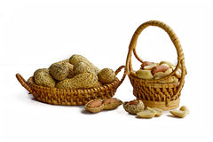 Peanuts in small wicker baskets and isolated on white Royalty Free Stock Images