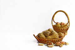 Peanuts in small wicker baskets and isolated on white Royalty Free Stock Photo
