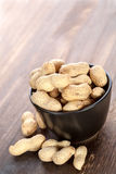 Peanuts on table and black bowl Royalty Free Stock Photos