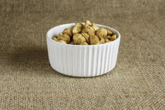 Peanuts In A White Bowl. A white bowl with peanuts on central display  on a hessian background Stock Photography