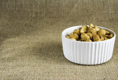 Peanuts In A White Bowl. A display of Peanuts in a white bowl  to the right on a hessian background Royalty Free Stock Image
