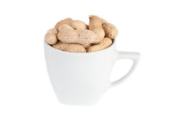 Peanuts in a white cup. Against a white background Royalty Free Stock Photography