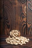 Peanuts on wood background. Peanut in shell texture and background. Peanuts texture. Healthy food. Close up view of shelled peanuts in wooden background Stock Photo