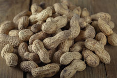 Peanuts on a wooden board. Low key, close-up royalty free stock image