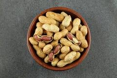 Peanuts in a wooden bowl. Peanuts in a wooden bowl on dark background Royalty Free Stock Image