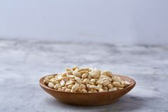 Peanuts in wooden plate isolated over white textured background, top view, close-up. Shelled peanuts in wooden plate isolated over white textured background royalty free stock photo