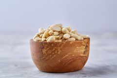 Peanuts in wooden plate isolated over white textured background, top view, close-up. Shelled peanuts in wooden plate isolated over white textured background stock image