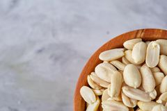 Peanuts in wooden plate isolated over white textured background, top view, close-up. Shelled peanuts in wooden plate isolated over white textured background stock images