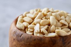 Peanuts in wooden plate isolated over white textured background, top view, close-up. Shelled peanuts in wooden plate isolated over white textured background royalty free stock photography