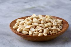 Peanuts in wooden plate isolated over white textured background, top view, close-up. Shelled peanuts in wooden plate isolated over white textured background royalty free stock photos