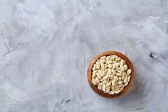 Peanuts in wooden plate isolated over white textured background, top view, close-up. Shelled peanuts in wooden plate isolated over white textured background stock photo