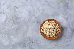Peanuts in wooden plate over white textured background, top view, close-up. Shelled peanuts in wooden plate over white textured background, top view, close-up royalty free stock photography